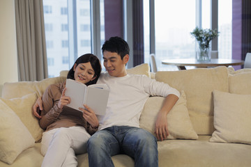 Young couple in living room reading a book together