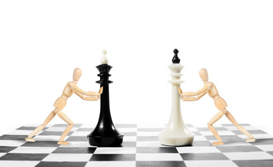 Chess game. Two men move kings on a chessboard. Concept with wooden puppets