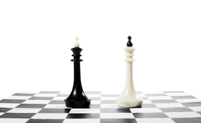 Two chess kings one in front of other. Battle of equal competitors. Concept with chess pieces against white background