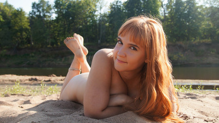 naked red-haired girl in the summer on river bank