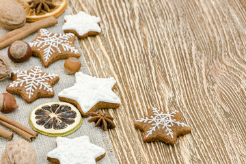 christmas homemade ginger cookies, nuts and spices on wooden board background