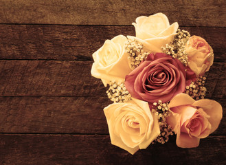 Beautiful roses in vintage style on wooden background