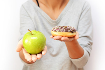 Healthy lifestyle or nutrition concept with young woman holding in hands an green apple and a donut