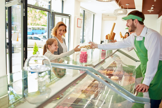 Vendor in confectionery shop selling desserts
