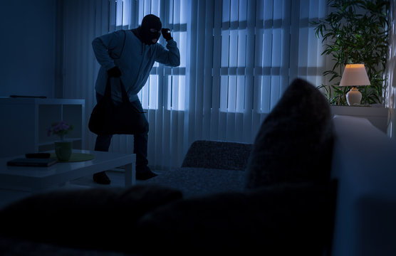 burglary or thief breaking into a home at night through a back d