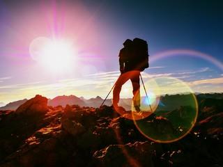 Lens flare defect.Man hiker with rucksack walk  on rocky peak. Man walking o