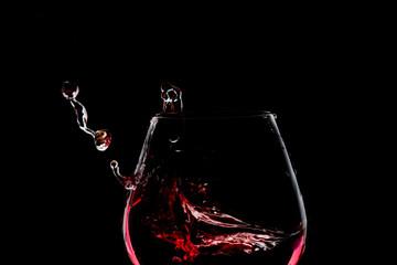 Splash of wine in the glass on dark backround