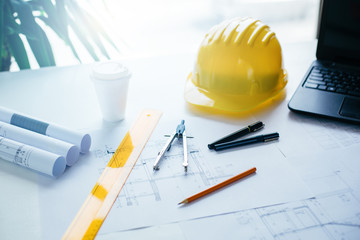 Construction equipment, blueprints and safety helmet on table