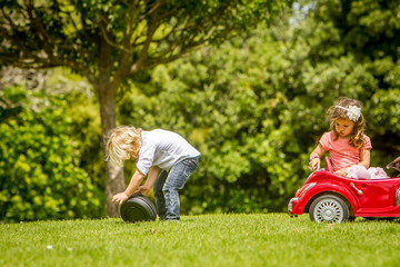 young happy children - boy and girl - driving a toy car outdoors