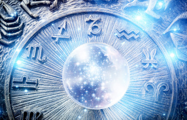 Wall Mural - a blue crystal ball with stars over zodiac background like astrology concept