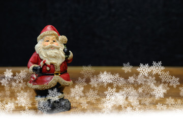 Santa claus statue and brown pine cone on wooden table with blac