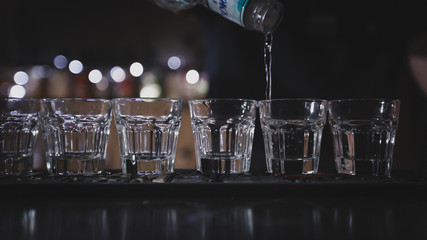 The bartender pours vodka into glasses