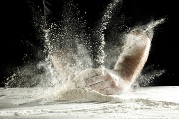 hands and splash of flour with black background