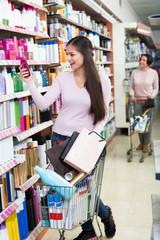 Cheerful young woman pushing shopping trolley