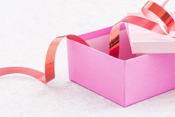 Gift wrapping for a holiday celebration, birthday or surprise party. Preparation of present with ribbon, box and decoration on table. Festive package material.