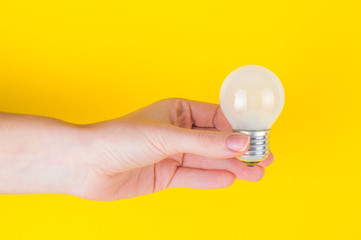 bulb in the hand on a yellow background