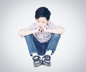 7 years old Asian boy is sitting and feeling sad isolated over gradient gray background.