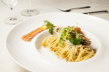 Spaghetti in white plate on dinning table