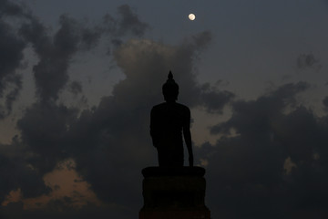 A moon shines in a sky over a large silhouetted Buddha statue in Bangkok, Thailand.