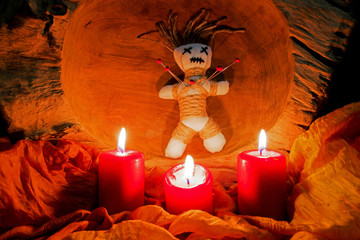 A voodoo doll with needles stands on an altar with candles