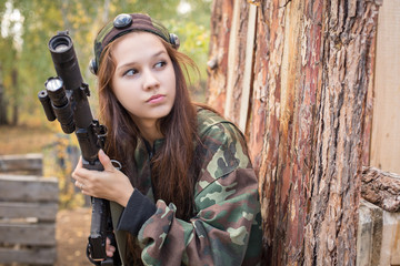 Young girl with a gun peeking from behind cover