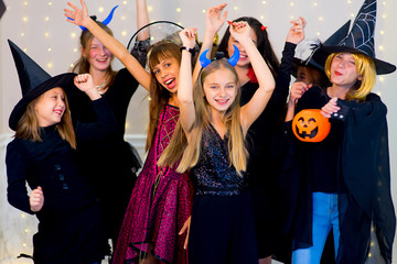 Happy group of teenagers dance in Halloween costumes
