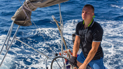 A young man the skipper controls the movement of sailing yachts during the boat race. Travel and luxury stay.