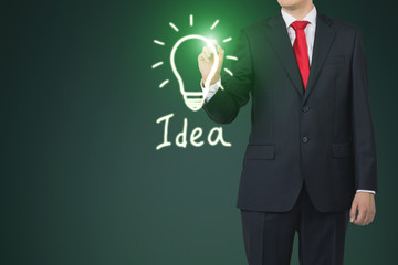 Close up of a businessman drawing a green light bulb sketch