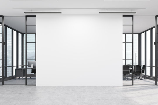 Office lobby with a large white wall and two meeting rooms