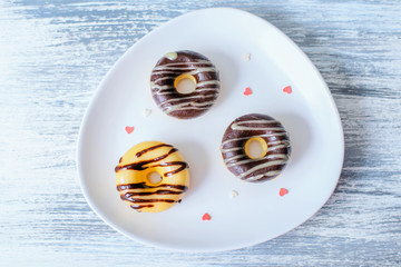Three Donuts on plate decorated with hearts
