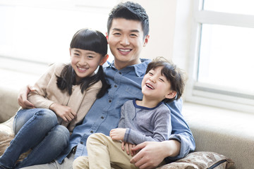 Happy young family resting in sofa