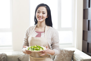 Portrait of smiling young woman holding a plate of prepared food