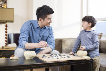 Little boy playing the game of Go with father