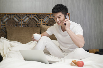 Young man talking on the phone in bed