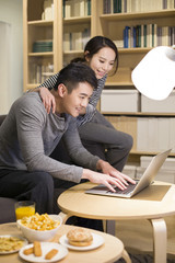 Young couple using laptop in living room