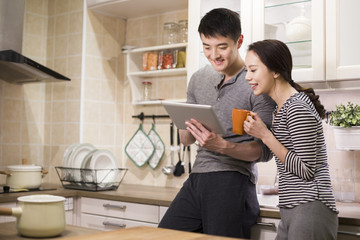 Young couple using digital tablet in kitchen