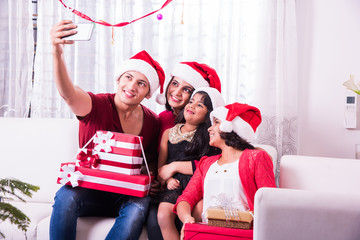 Young happy indian or asian family of four taking a photo of themselves by smartphone or mobile phone Christmas eve, merry christmas