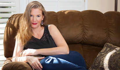 Mature Blonde Female Sitting on Couch Wearing Black Top Jeans
