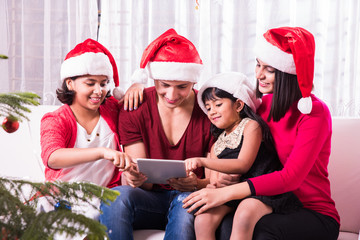 Young happy indian or asian family of four taking a photo of themselves by smartphone or mobile phone or tablet computer on Christmas eve, merry christmas