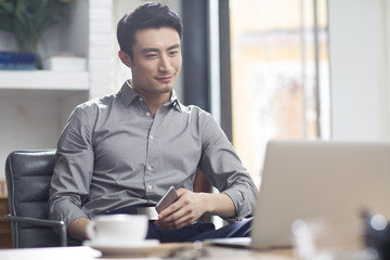 Young businessman working on laptop while sitting in office