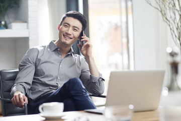 Young businessman talking on mobile phone in office
