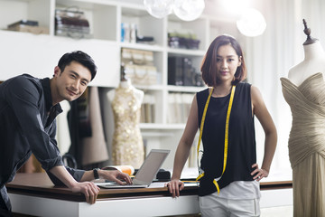 Portrait of two young fashion designers working in fashion boutique