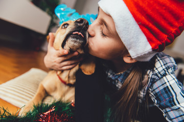 Girl with santa hat kissing dog