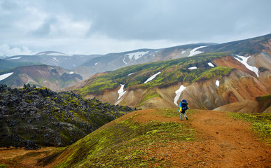 hiker on the trail in the Islandic mountains. Trek in National Park Landmannalaugar, Iceland.