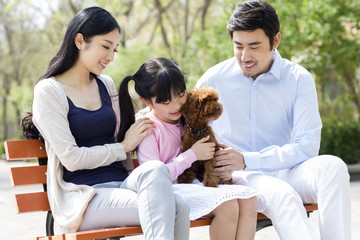 Happy young family playing with their pet dog outdoors