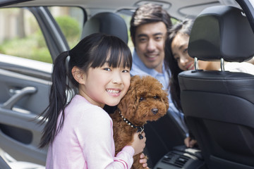 Happy young family with their pet dog sitting in car