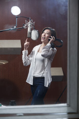 Young woman singing in recording studio