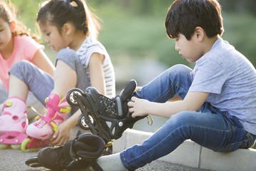 Happy children putting on inline skates