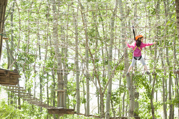 Little girl playing in tree top adventure park