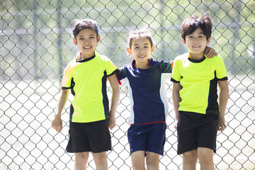 Happy children in sportswear leaning against chainlink fence